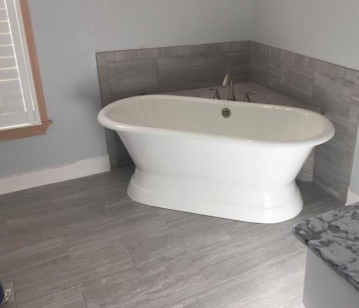 Remodeled bathroom with gray tile and a new stand alone tub.